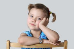 Little girl. Small girl sits on chair Stock Photos
