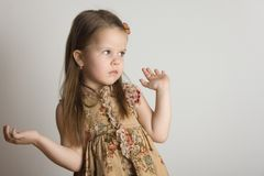 Little girl. Hands up, gray background Royalty Free Stock Images