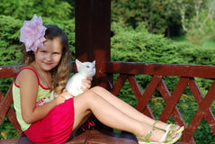 The little girl. With a white kitten on a bench Stock Photo