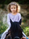 Little girl. During a ride on horse Stock Photography