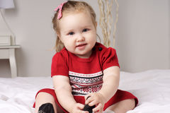 Little girl. Calm little girl in red dress sitting on parent's bed Stock Photography