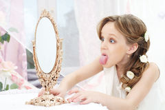 Little girl. Beautiful little girl with mirror showing her tongue Stock Photography