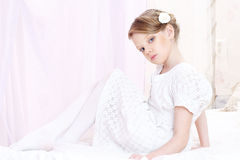 Little girl. Little beautiful caucasian girl sitting on bed and posing like ballerine Royalty Free Stock Images