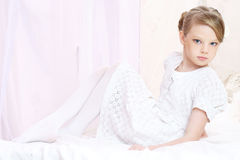 Little girl. Little beautiful caucasian girl sitting on bed and posing like ballerine Royalty Free Stock Photos