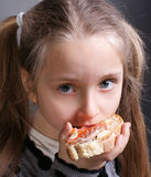 Little girl. Eating bread and butter with fish on a gray background Royalty Free Stock Photos