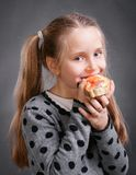 Little girl. Happy little girl eating bread and butter with fish on a gray background Royalty Free Stock Images