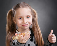 Little girl. Happy little girl eating bread and butter with fish and showing yes sign on a gray background Stock Photos