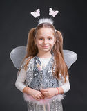 Little girl. Happy small girl dressed up as a fairy on a gray background royalty free stock image