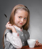 Little girl. With cup of tea holding a spoon in hand on a gray ackground Stock Image