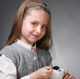 Little girl. With cup of tea holding a spoon in hand on a gray ackground Royalty Free Stock Photos