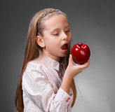 Little girl. Eating an apple on a gray background royalty free stock images