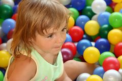 The little girl. On a background of multi-coloured balls Stock Images