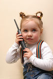Little girl. Little talking girl with phone over interior wall Stock Images
