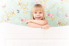 Little girl. Little adorable girl with a sly smile standing behind a bed Stock Photo