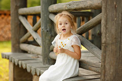 Free Little Girl 5 Years Blonde Sitting On A Log Home, Holding Hands Royalty Free Stock Images - 91079909
