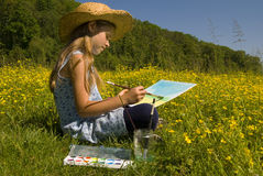 Little girl. Painting a picture in a beautiful field Royalty Free Stock Photos