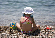 Little girl 7. Little girl sitting on the shore of sea Stock Images