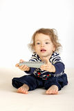 A little girl. A little girl presses on a stand and switches on a television set Stock Photo