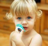 Little girl. Little curly girl holding her dummy Stock Image