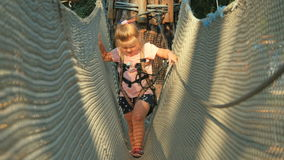 Little girl accuracy moves on the rope`s way in rope park. Little cute girl spends her leisure time at the nature. Cute girl in special equipment climbing on the stock video