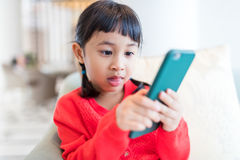 Little girl addicted to using cellphone stock photo
