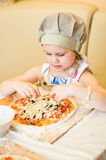 Little girl adding cheese in pizza Stock Images