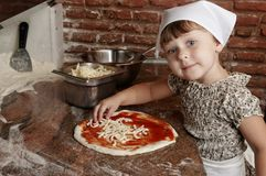Little girl adding cheese to pizza. Stock Photos