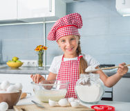Little girl adding flour to a dough Stock Photography