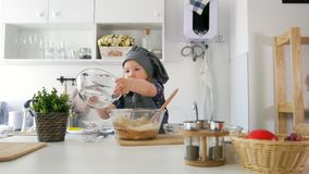 Little girl adds ingredients to the pastry dough. Close up stock video footage
