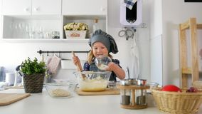 Little girl adds oatmeal to the pastry dough. Close up stock video