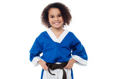 Little girl adjusting her brown karate belt Stock Photos