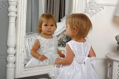 Little girl  admires her reflection in mirror Stock Images