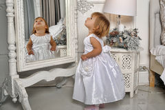 Little girl  admires her reflection in mirror Stock Image