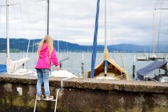 Little girl admiring beautiful yachts in a harbor of Lindau, a town on the coast of Bodensee lake in Germany on cloudy autumn day. Little girl admiring beautiful Royalty Free Stock Photos