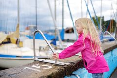Little girl admiring beautiful yachts in a harbor of Lindau, a town on the coast of Bodensee lake in Germany on cloudy autumn day. Little girl admiring beautiful Royalty Free Stock Photography