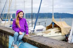 Little girl admiring beautiful yachts in a harbor of Lindau, a town on the coast of Bodensee lake in Germany on cloudy autumn day. Little girl admiring beautiful Royalty Free Stock Photo