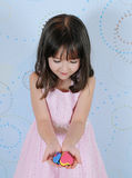 Little girl admiring heart shapes in her hands Stock Image