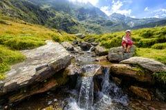 Little girl admiring a mountain creek Royalty Free Stock Photography