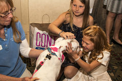 Little Girl Adopts Rescued Humane Society Pet Dog. Girl hugs the dog her family adopted at the Compassion with Fashion Luncheon and Fashion Show benefiting the royalty free stock photography