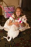 Little Girl Adopts Rescued Humane Society Pet Dog. Girl hugs the dog her family adopted at the Compassion with Fashion Luncheon and Fashion Show benefiting the stock photography