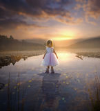 Little girl and adult reflection. A little girl looks down at her reflection of an older woman royalty free stock photo