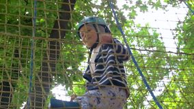 Little girl in the adventure park. Rope suspension bridge extreme sport entertainment leisure activity physical exercise forest trees child. little girl female stock footage