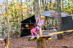 Little girl in Adventure Park. Little girl is zip lining in the adventure park Royalty Free Stock Image