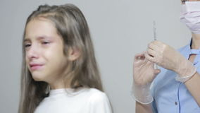 Little girl is afraid of the doctor with a syringe. baby cries afraid injection stock footage