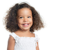 Little girl with an afro hairstyle smiling and wearing a white dress Stock Photography