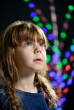 The little girl against a dark background looks aside Royalty Free Stock Photography