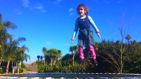 Little girl age 05 Jumping on a trampoline stock video footage