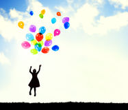 Little Girl in the Air Holding Balloons Stock Images