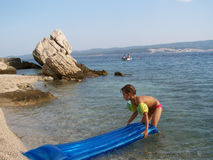Little girl with air mattress on the beach. Rocky croatian beach with a little girl, holding air mattress Stock Photos