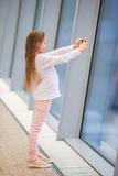 Little girl in airport near big window while wait for boarding. Little kid together in airport waiting for boarding Royalty Free Stock Photo